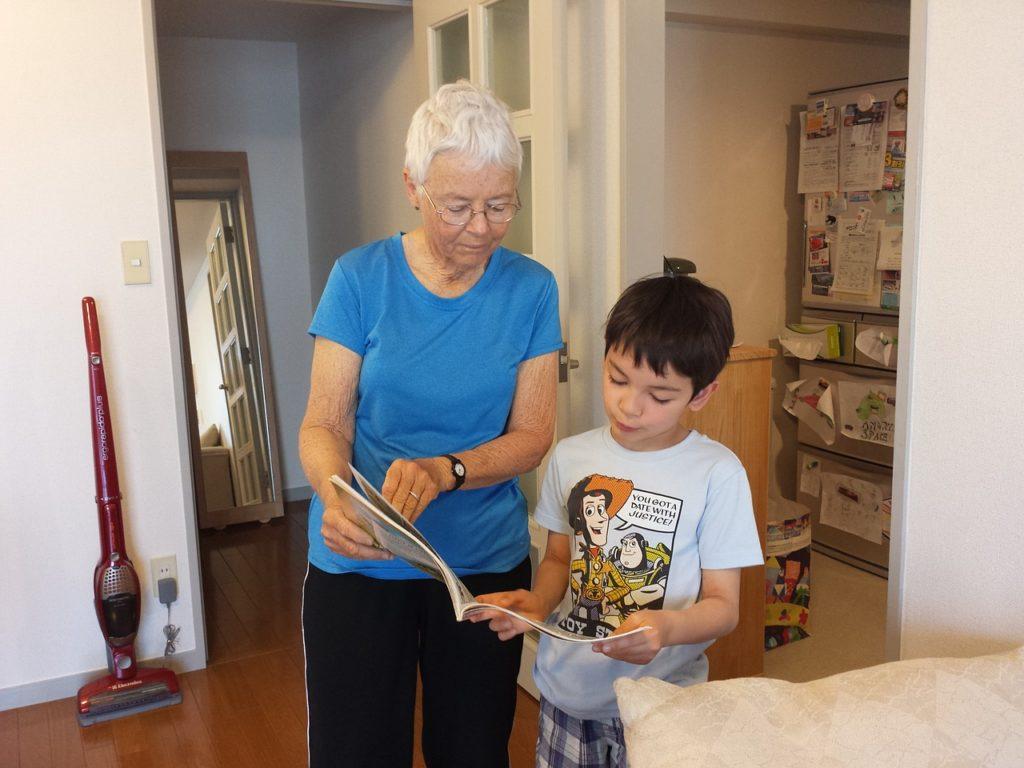 Entraide (lecture) entre grand-mère (senior) et petit-fils (junior)